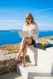 Frau, die Laptop während im Urlaub in Mittelmeer verwendet Stockfotografie