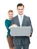 Frau, die in Laptop während Kerlholding es zeigt Stockbild