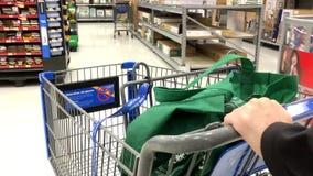 Frau, die Laufkatze drückt, um Waren bei Walmart zu kaufen stock video