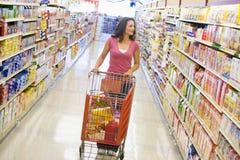 Frau, die Laufkatze entlang Supermarktgang drückt Stockbild