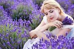 Frau, die am Lavendelfeld im weißen Kleid sitzt Lizenzfreie Stockbilder