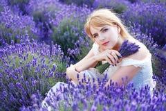 Frau, die am Lavendelfeld sitzt Stockbilder