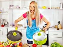 Frau, die Lebensmittel an der Küche zubereitet. Lizenzfreies Stockfoto