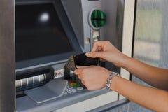 Frau, die leere Geldbörse nahe ATM-Maschine hält Konzept des Seins brach lizenzfreie stockfotografie