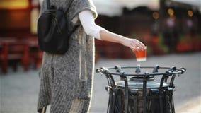 Frau, die leere Kaffeetasse auf dem Abfall an der Straße in der Stadt, auf einem gemütlichen Café des Hintergrundes wirft stock video