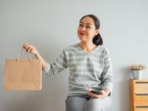 Frau, die leere Papiert?te des Produktes vorf?hrt, das sie online kaufte Konzept des Onlineeinkaufens stockbilder