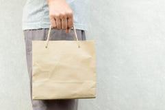 Frau, die leeres braunes Papiertütepaket hält Stockfoto