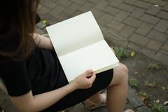 Frau, die leeres Buch im Garten liest Stockbild