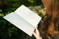 Frau, die leeres Buch im Garten liest Lizenzfreie Stockfotos