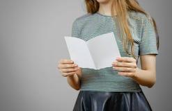 Frau, die leeres weißes Fliegerpapier zeigt Broschürendarstellung pam lizenzfreie stockfotografie