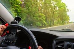 Frau, die Lenkrad, Antriebe das Auto hält lizenzfreies stockbild
