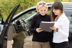 Frau, die Lieferung ihres Neuwagens entgegennimmt Stockfotografie
