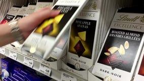 Frau, die Lindt-Schokolade kauft und Bestandteile liest stock video