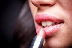 Frau, die Lippenstift anwendet stockbilder