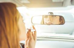 Frau, die Lippenstift in das Auto einsetzt lizenzfreies stockbild
