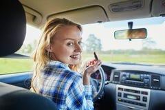 Frau, die Lippenstift in einem Auto beim Fahren anwendet Stockbild