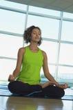 Frau, die in Lotus Position At Gym sitzt Lizenzfreie Stockfotografie
