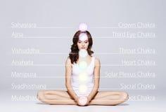 Frau, die in Lotus Position meditiert Farbige chakra Lichter über ihrem Körper Yoga, Zen, Buddhismus, Wiederaufnahme und Wohl Stockfotos