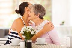 Frau, die ältere Mutter umarmt Stockbild