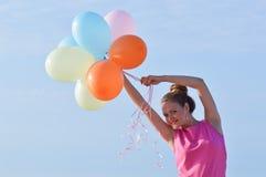Frau, die Luftballone hält Stockfoto