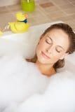 Frau, die in Luftblase gefülltem Bad sich entspannt Lizenzfreies Stockfoto