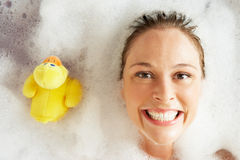 Frau, die in Luftblase gefülltem Bad sich entspannt Lizenzfreie Stockbilder
