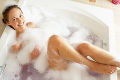 Frau, die in Luftblase gefülltem Bad sich entspannt Lizenzfreies Stockbild