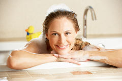 Frau, die in Luftblase gefülltem Bad sich entspannt Lizenzfreie Stockfotografie