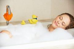 Frau, die in Luftblase gefülltem Bad sich entspannt Stockbild