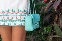 Frau, die Luxus-snakeskin Pythonschlangenhandtasche hält Bali-Insel Modetaschenkonzept auf einer Tropeninsel lizenzfreie stockbilder