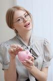 Frau, die Münze in ein Sparschwein einfügt Lizenzfreie Stockfotos