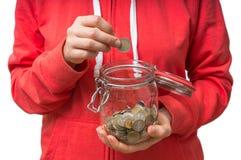 Frau, die Münze in Geldglas für unerwartete Ausgaben setzt stockfoto