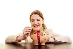 Frau, die Münzen in piggy Querneigung einsetzt stockbild