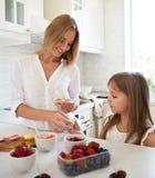 Frau, die macarons an der Küche mit ihrer kleinen Tochter kocht Lizenzfreie Stockfotos