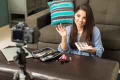 Frau, die Make-up auf Kamera setzt Stockfotos