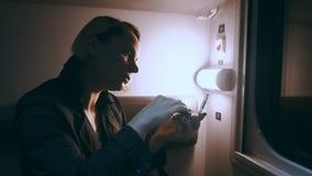 Frau, die Make-up beim Reisen mit dem Zug tut stock footage