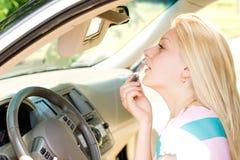 Frau, die Make-up in einem Auto anwendet Lizenzfreies Stockbild