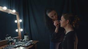 Frau, die Make-up für ein Mädchen nahe Spiegel anwendet stock footage