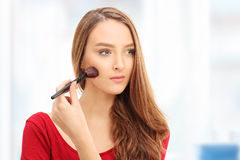 Frau, die Make-up mit einer Bürste anwendet Stockbilder