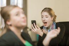 Frau, die Make-up unter Verwendung ihres Telefons als Spiegel anwendet stockbilder