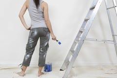 Frau, die Malerpinsel gegen Wand im Haus hält Lizenzfreies Stockbild