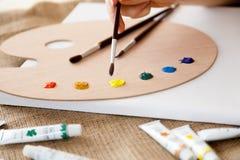 Frau, die Malerpinsel hält und Farbe auf der Palette wählt Lizenzfreie Stockfotografie