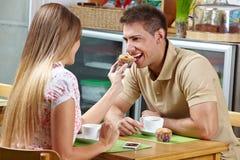 Frau, die Mann ein Muffin schmecken lässt lizenzfreie stockfotos