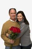 Frau, die Mann mit roten Rosen umarmt Lizenzfreies Stockfoto