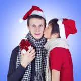 Frau, die Mann mit Weihnachtsgeschenkkasten küßt Stockbild
