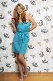 Frau, die Martini gegen Blumendruck-Wand trinkt Lizenzfreies Stockfoto