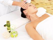 Frau, die Massage des Gesichtes im Badekurortsalon hat Stockfotografie