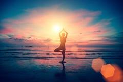Frau, die Meditation nahe dem Ozeanstrand tut Stockfotos