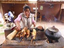 Frau, die Meerschweinchen auf offenem Feuer kocht lizenzfreie stockbilder