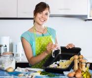 Frau, die merluccid Hechtdorsche zubereitet Stockfotos